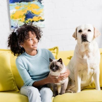Uma criança sentada no sofá com o gato ao colo e o cão ao lado.